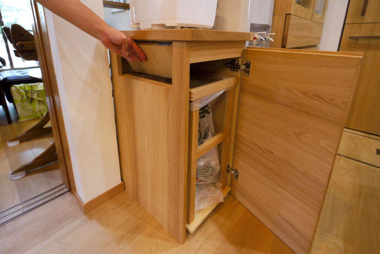 オーダーキッチンのゴミ箱です。キッチンのリフォーム、改装になります。タモ材で製作しました。天板の上を使えるようにしてあります。ゴミを入れる所にバネを仕掛けてあり、蓋が閉まるようになっています。ゴミ袋は取り出し易いようになっています。