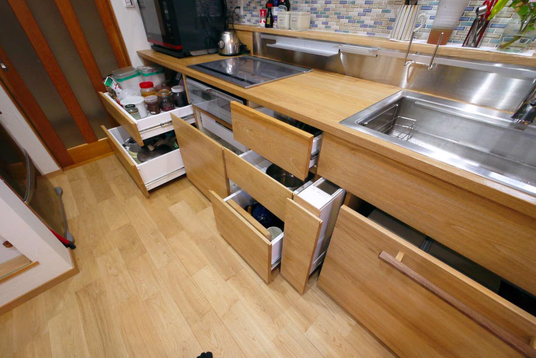 オーダーキッチンです。キッチンのリフォーム、改装になります。天板、扉には無垢のタモ材を使っています。引出しの奥行は60cmあり、たっぷり収納出来ます。ソフトクローズ機能付きです。米びつのスライド収納もあります。シンクの下はゴミ箱のワゴンになっています。